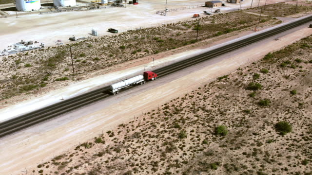 drone footage of a two-lane highway in west texas oil and gas fracking country with industrial vehicles and semi trucks - texas stock videos & royalty-free footage