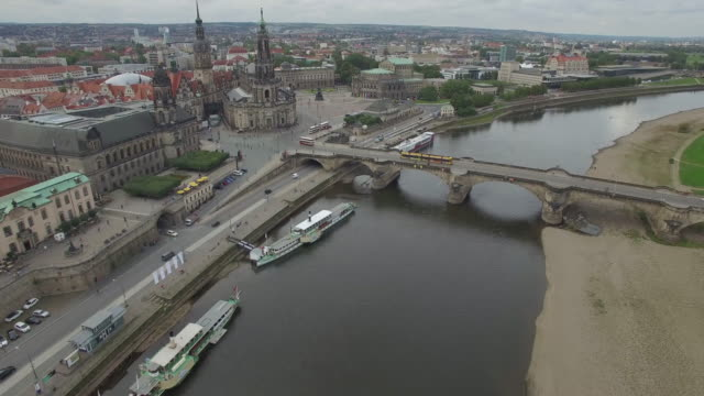 Drone footage of bridge over river by cityscape
