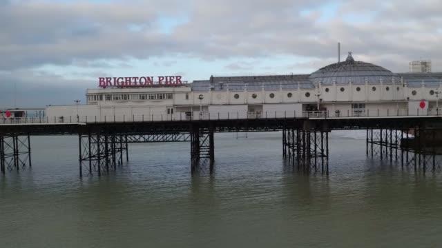 drone footage of brighton pier and beach; england: east sussex: brighton: ext air views / aerials drone footage of brighton pier and beach - ブライトン パレスピア点の映像素材/bロール