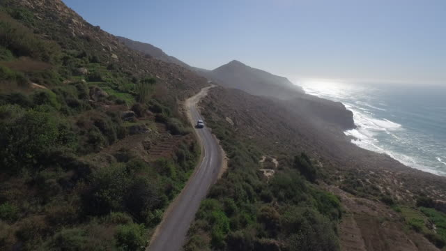 Drone footage of car moving on mountain road against blue clear sky