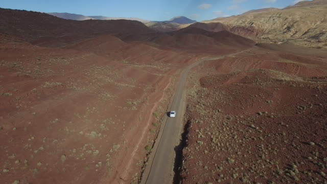 drone footage of car moving on road amidst arid landscape - mountain road stock videos & royalty-free footage