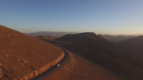 drone footage of car moving on winding road amidst arid landscape during sunset - sports utility vehicle stock videos & royalty-free footage