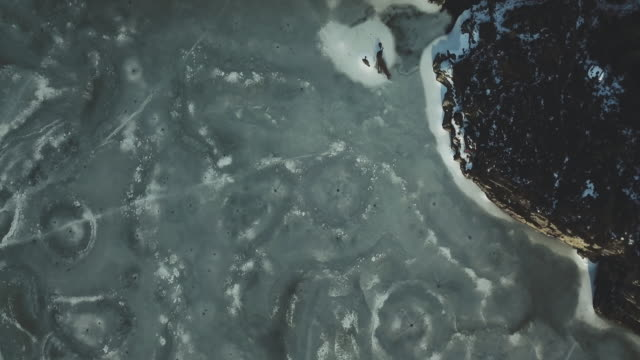 drone footage of cracks and craters on the ice of a frozen lake. - meteor stock videos & royalty-free footage