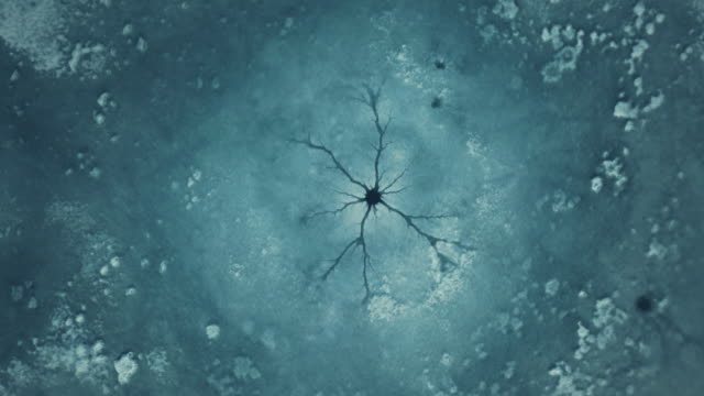 drone footage of cracks and craters on the ice of a frozen lake. - kälte stock-videos und b-roll-filmmaterial