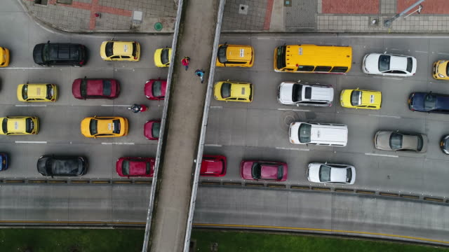 drone footage of footbridge over traffic moving on highway, bogota, colombia - bogota stock videos & royalty-free footage