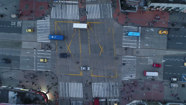 Drone footage of land vehicles and people moving on street in city, Bogota, Colombia