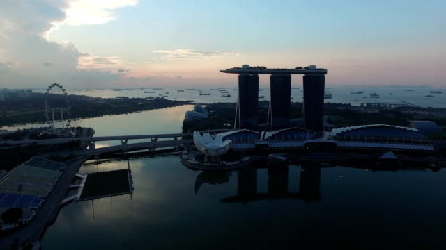 drone footage of marina bay, singapore at sunrise - marina bay sands stock videos and b-roll footage