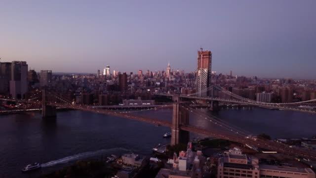 Drone footage of New York City's Brooklyn Bridge at night.