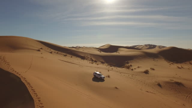vídeos de stock e filmes b-roll de drone footage of off-road vehicle parked in desert - marrocos
