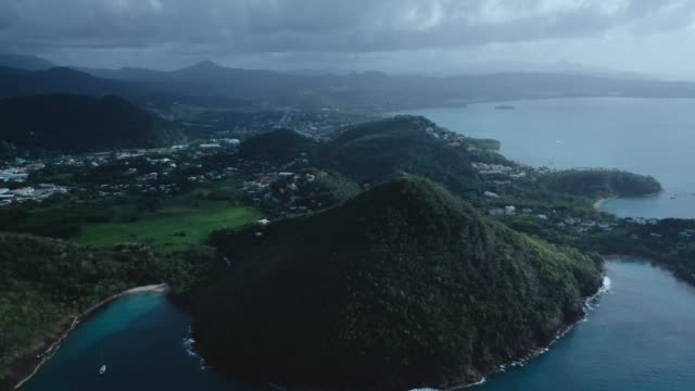 vidéos et rushes de drone footage of panorama of the city on a hilly island and yachts in the sea on a cloudy day (saint lucia) - arbre tropical