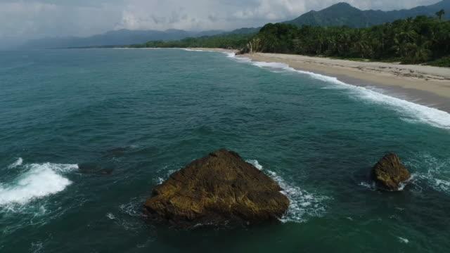 drone footage of sea waves rushing towards shore at beach, tayrona national park, colombia - tayrona national park stock videos and b-roll footage