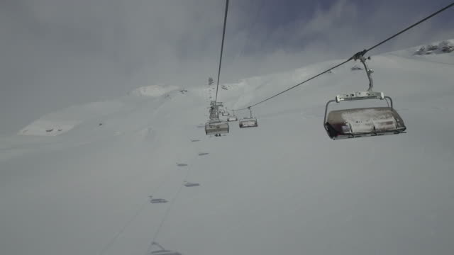 Drone footage of ski lifts moving over snowcapped mountain