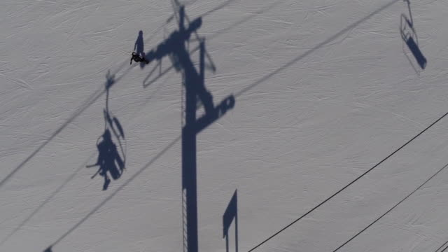 drone footage of skiers on ski lifts in skiing region, whistler, canada - skiing and snowboarding stock videos and b-roll footage