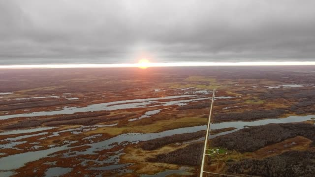 drone footage of sunset, field, small lakes, road, settlement and forests (north shoal lake, manitoba, canada) - マニトバ州点の映像素材/bロール