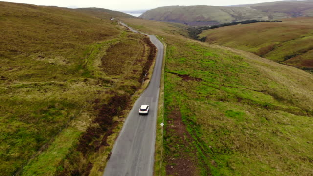 drone footage of suv car driving in the roads of the scottish highlands during travel. - sports utility vehicle stock videos & royalty-free footage