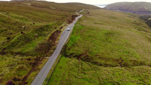 drone footage of suv car driving in the roads of the scottish highlands during travel. - rural scene stock videos & royalty-free footage