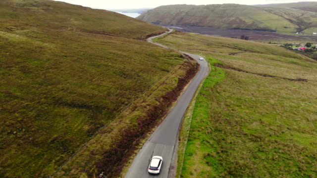 drone footage of suv car driving in the roads of the scottish highlands during travel. - scottish highlands stock videos & royalty-free footage