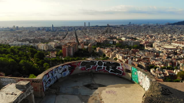 vidéos et rushes de drone footage of the military bunkers viewpoint over barcelona city during sunrise. - barcelone espagne
