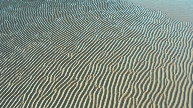 drone footage of the ripple pattern on a scottish beach in south west scotland after the tide has went out - tide stock videos & royalty-free footage