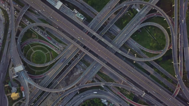 drone footage of top view of highway road junctions. the intersecting freeway road overpass the eastern outer ring road of bangkok, thailand.zoom out shot - ponte video stock e b–roll