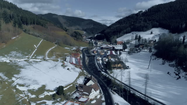 drone footage of town in valley amidst mountains during winter, kniebis, black forest, germany - バーデン・ビュルテンベルク州点の映像素材/bロール