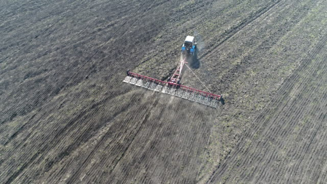 Drone footage of tractor sowing spring seeds