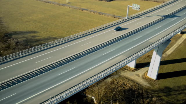 Drone footage of vehicles moving on highway bridge on sunny day, Wuerzburg, Bavaria, Germany