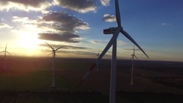 Drone footage of wind turbines stand on the Innogy SE wind farm as the Garzweiler open cast lignite mine operated by RWE AG sits beyond in Bedburg...
