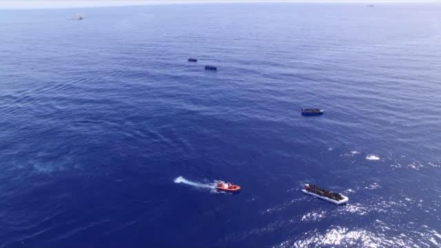 vídeos y material grabado en eventos de stock de drone footage showing several migrant boats floating off the italian coast in 2017 before rescue - bbc