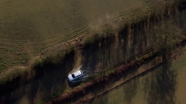 drone footage shows vehicles negotiating the flooded b4069 road at christian malford in wiltshire after the river avon has burst its banks. parts of... - car stock videos & royalty-free footage