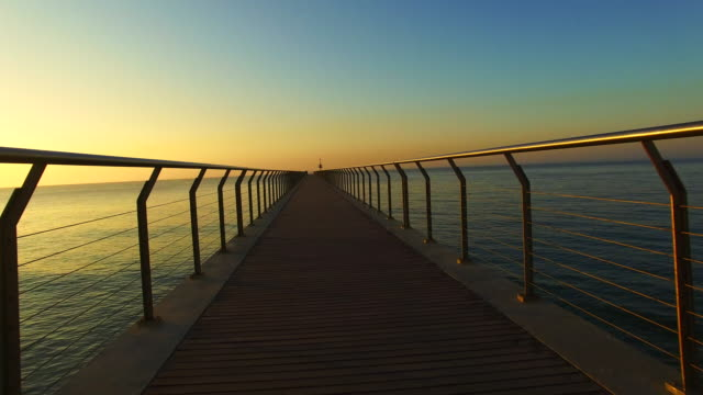 Drone footage with motion view flying over a long dock with nice vanishing point during sunrise in the Mediterranean sea. 4K UHD.