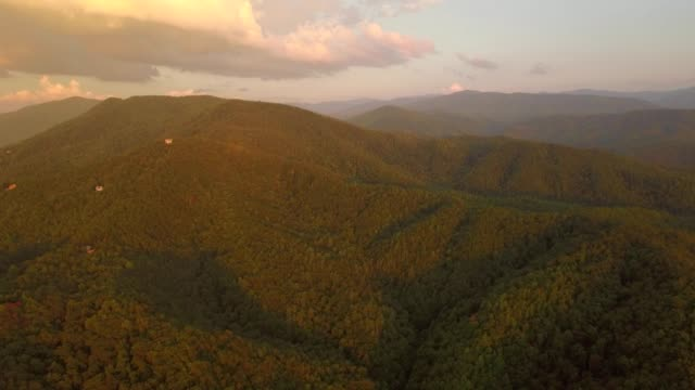 drone - houses dot a mountain side wilderness at dusk - hill stock videos & royalty-free footage