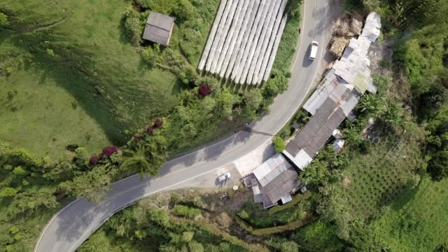 A drone hovers birdseye over a road in a small town in Medellín Antioquia Colombia