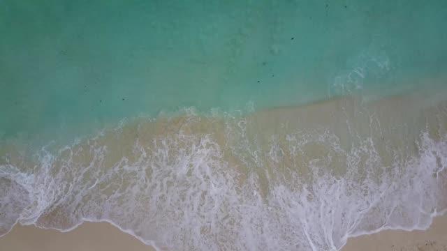 vídeos y material grabado en eventos de stock de a drone hovers birdseye over waves crashing on the shore of a beach in cancún quintana roo mexico - quintana roo