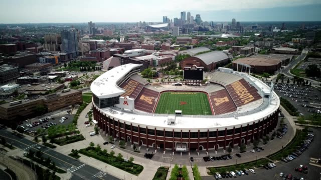 vidéos et rushes de a drone hovers by a college football stadium in view of downtown minneapolis minnesota - minnesota