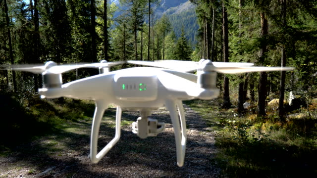 a drone hovers in front of the camera in a lush alpine forest environment. - following stock videos & royalty-free footage