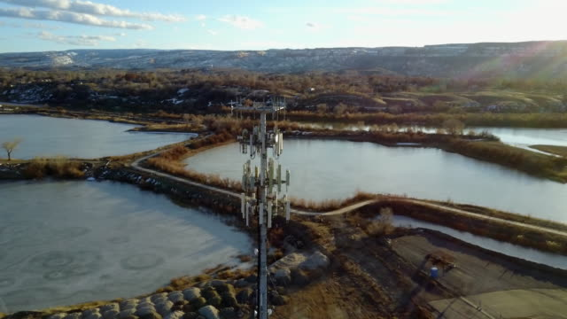 drone image of a cellular tower in front of lakes - telephone pole stock videos & royalty-free footage