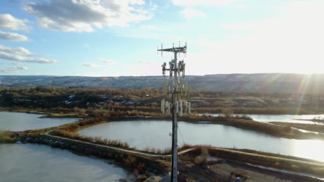 drone image of a cellular tower in front of lakes - repeater tower stock videos and b-roll footage