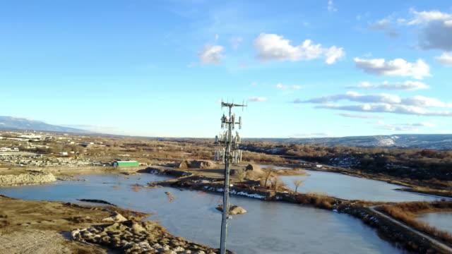 vídeos de stock e filmes b-roll de drone image of a cellular tower in front of lakes - poste de telégrafo