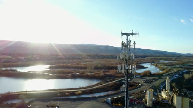 drone image of a cellular tower in front of lakes - pole stock videos and b-roll footage
