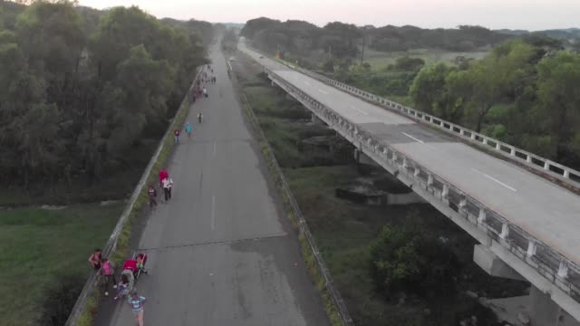 drone images show a caravan of central american migrants walking along a highway in the mexican state of chiapas as they head toward the united states - convoy stock videos & royalty-free footage