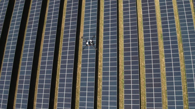 drone inspecting a solar farm - solar panels stock videos & royalty-free footage