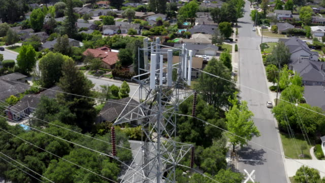 drone is flying around  high voltage power transmission tower with communication equipment on a sunny day in cupertino, california. - pole stock videos & royalty-free footage