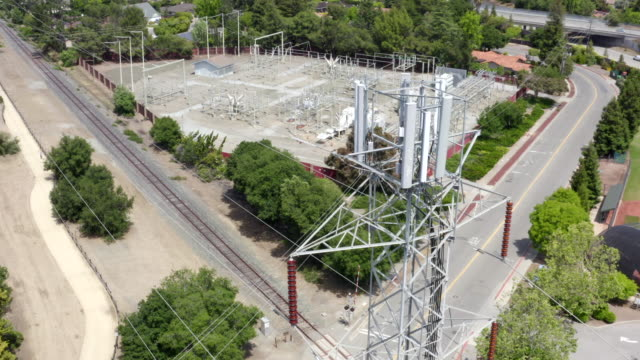 drone is flying around  high voltage power transmission tower with communication equipment on a sunny day in cupertino, california. - power cable stock videos & royalty-free footage
