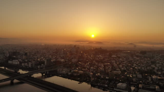 a drone is flying beside the sunrise city. wakayama city. - 日の出点の映像素材/bロール