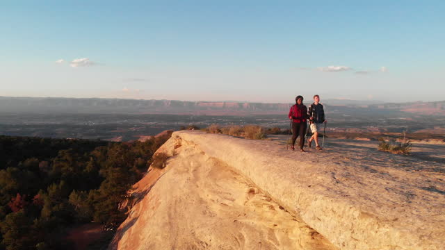drone leads a mixed-race couple as they hike along a - western usa stock videos & royalty-free footage