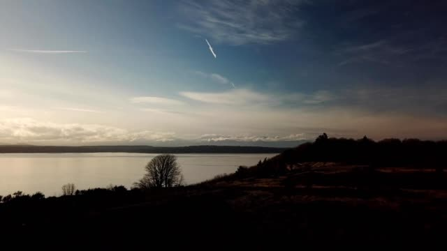 A drone looks out over Puget Sount at sunset in Seattle Washington