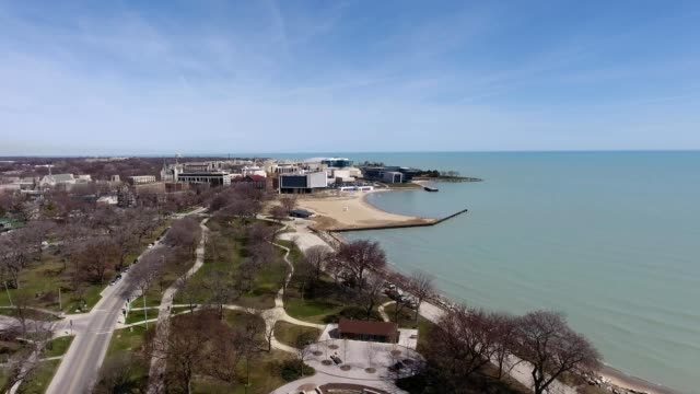 a drone looks over a lake towards a university in evanston illinois - illinois stock videos & royalty-free footage