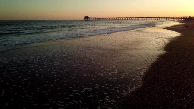 a drone low flies over a shoreline in view of a sunset lit pier in atlantic beach north carolina - north carolina beach stock videos & royalty-free footage