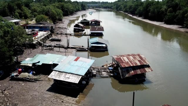 a drone low flies over fisherman village on masai river johor malaysia - johor stock videos & royalty-free footage